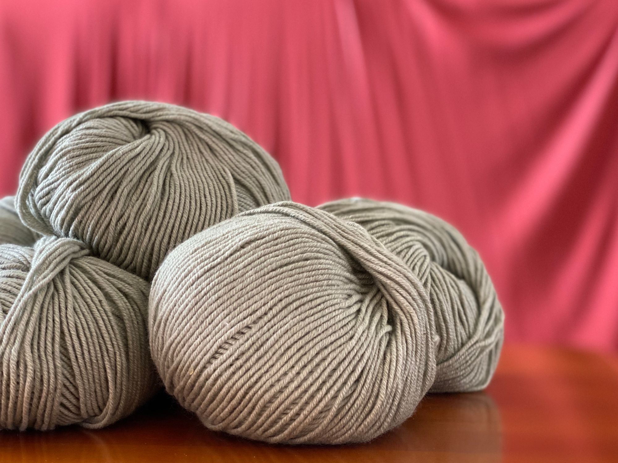 balls of yarn in a light sage green against a rich coral draped fabric background