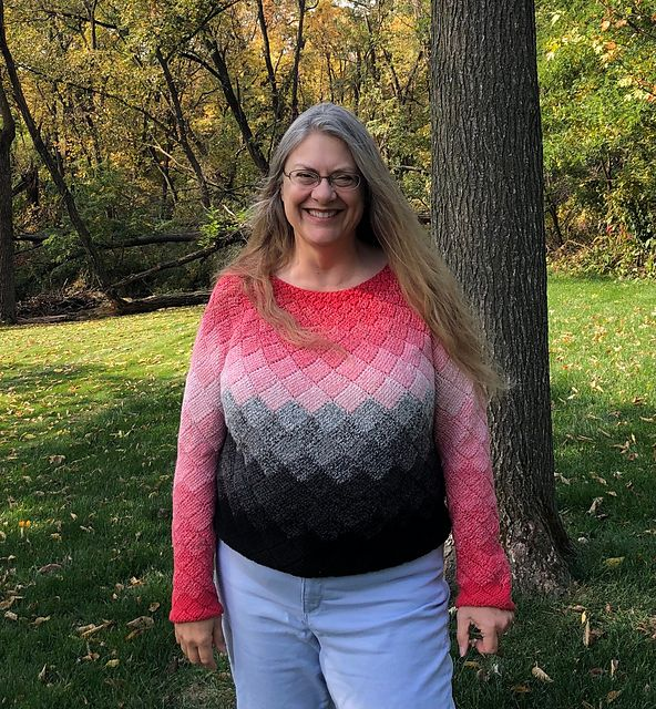 A woman with a bold smile stands showing off her crocheted pink, grey, and black gradient sweater.