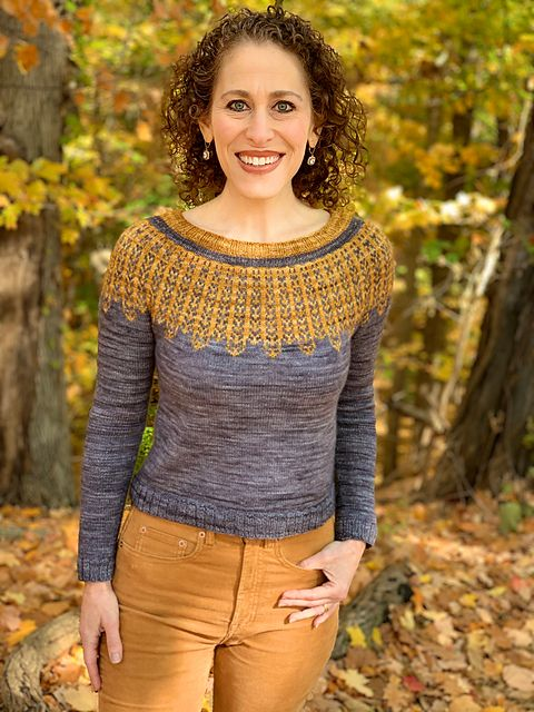 A smiling woman in a grey sweater with a gold colorwork yoke motif that pays homage to Ruth Bader Ginsberg's collars.