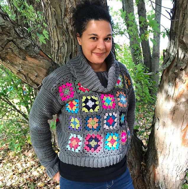 A woman wearing a crocheted cowl-neck sweater in grey with bright granny squares stands in front of a tree, smiling at the camera.