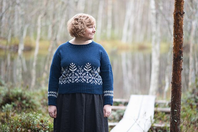 A woman stands in a forest, near a lake, wearing a rich blue and white colorwork sweater.