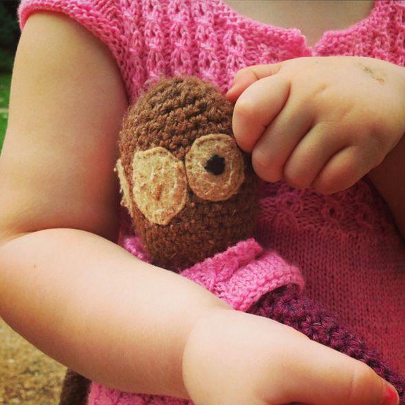 Marlowe and her favorite stuffed monkey wearing matching handknit pink dresses.