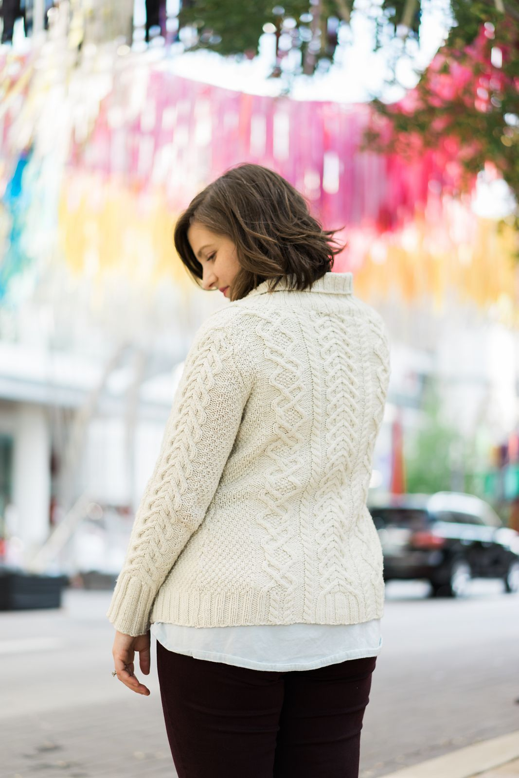 Christina in a cream-colored handknit cabled cardigan