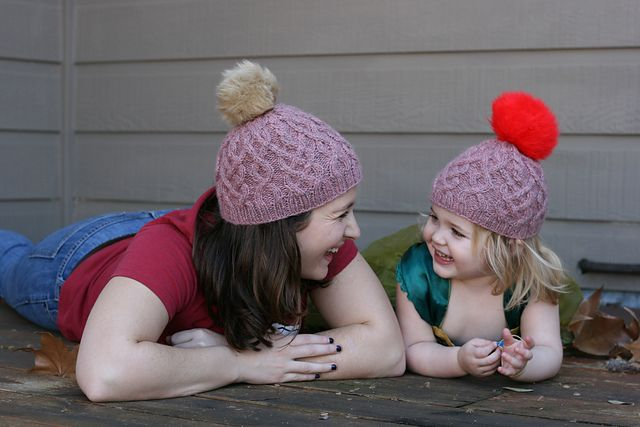 Christina and Marlowe smiling at each other in their matching Habitat hats with giant pom poms