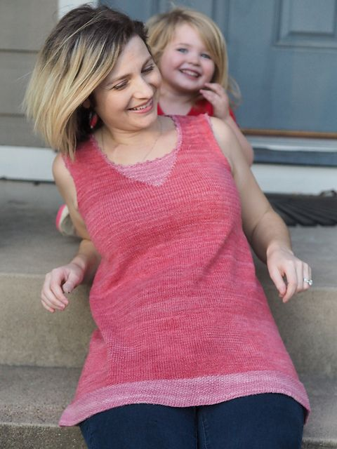 Christina and Marlowe, smiling on their porch, Christina wearing a pink handknit tunic