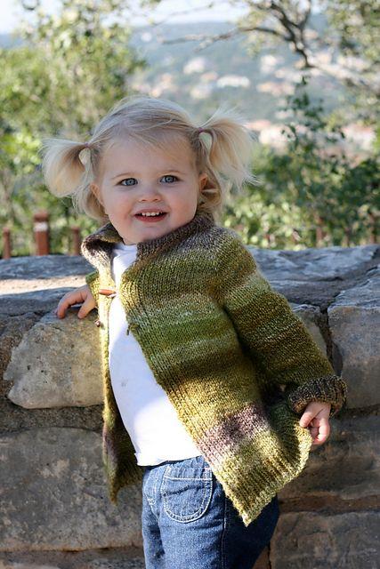 Marlowe smiling in her handspun, handknit cardigan, made by Christina